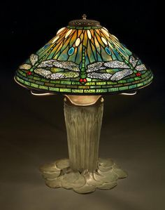 A Fine Tiffany Favrile glass and bronze dragonfly lamp on a cattail base 1899-1920 the shade with seven overlapping dragonflies with bodies in emerald green and ruby red eyes against a ground shading from striated pink/purple to blue to green with opalesecent white and cobalt blue cabochon jewels, the base cast with upright cattails and overlapping lily pads