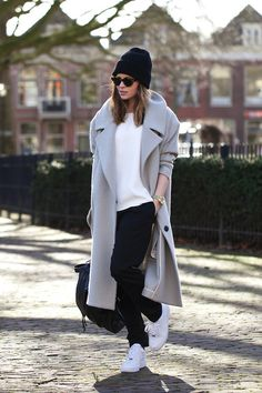 Shop this look for $188:  http://lookastic.com/women/looks/crew-neck-t-shirt-and-coat-and-sweatpants-and-beanie-and-backpack-and-athletic-shoes-and-watch-and-sunglasses/2615  — White Crew-neck T-shirt  — Grey Coat  — Black Sweatpants  — Black Beanie  — Black Leather Backpack  — White Athletic Shoes  — Gold Watch  — Black Leopard Sunglasses
