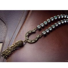 "Vintage inspired, Equestrian made. 24"" of luxurious brass clad Swarovski Cup Chain that hangs a Fer a Cheval Medallion and the finishing touch is the Bordeaux tassel!   In total length it is 30"" long. It's the perfect weight to wear with a tunic or over your Fall cape or poncho. Caracol Silver - Price: $334.00"