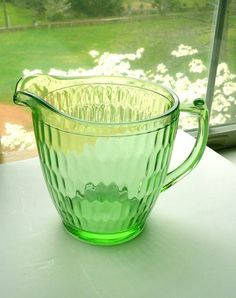 Vintage Depression Glass Pitcher Jeannette This lovely vintage Depression green glass pitcher is made by the Jeannette Company between 1928 - 32. The pattern is Hex Optic or Honeycomb.Quite heavy for being 5 1/2 inches tall  7 inches wide from mouth - handle. Holds 4 cups