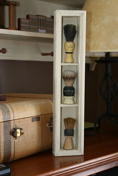 Vintage shaving brush display. My husband actually uses a shaving brush... how cool would this look in our new bathroom?!?