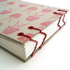 Handbound sketchbook with chevron patterned stitching, with raw bookboard cover stamped with Eames chairs! by @ruthbleakley
