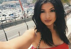 Kylie wearing bright red and a dark brown lip with should length jet black hair