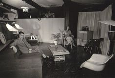 """Roy and Patricia Hamma enjoy time in their living room, furnished with Charles and Ray Eames pieces. Once the couple's MHA 111 model was complete, Roy Hamma, an attorney, hired a professional photographer to document their newly built home, which was one of the original 30 """"guinea pig"""" properties. The MHA cooperative purchased 800 acres of land on the Brentwood side of the Santa Monica Mountains and worked with modernist architects A. Quincy Jones and Whitney R. Smith and structural ..."""