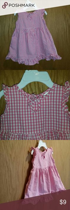 Pink Gingham Baby Gap Dress Adorable little baby dress with ruffle details on the shoulders and hemline. Has a really cute eyelet opening on the front- the tie on that has slight fraying but can be cut off and you'd never know. The back has flower buttons which look great! Very light wear and has been gently worn. Baby Gap Dresses Casual