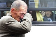 """A North Korean man waves his hand """"Good bye"""" as a South Korean relative weeps. Likely the last time they will ever meet again."""