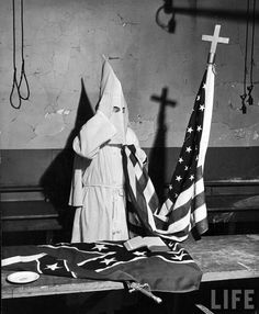 A member of the Ku Klux Klan stands beside a U.S. flag. In front of the robed figure is a Confederate battle flag, and a noose hangs in the back, 1946. Photo credit: Life Magazine