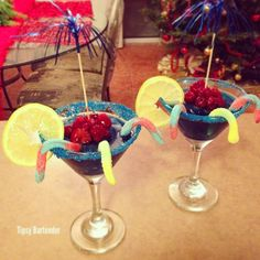BLUE RASPBERRY CRAWLER Tequila Raspberry Sourpuss Blue Curacao Ginger Ale Cranberry Juice Ice Blended  Garnish: Sour Gummy Worms Frozen Raspberries