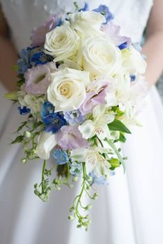 soft cascade of ivory roses,white alstroemeria,lavender lisianthus and blue delphinium