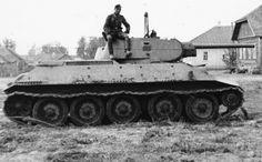Немецкий офицер сидит на башне брошенного советского танка Т-34