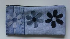 Pencil case, zip which has been reused from a pair of jeans. Ironed a waistband out and sewed to a strip of denim. Flowers made from denim.