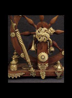 (Detail) ETONNANT PETIT ROUET DE PRESENTATION XIXème  Noyer et bronze doré. Ce rouet est habillé de tout un ensemble d'éléments de bronze du début du XIXème. Un élément est même gravé d'initiales, probablement celui qui l'a fait. Le rouet pouvait fonctionner bien-sûr.  Très bon état. Belle dorure des éléments. Deux ou trois petits éclats dans le bois.  Dimensions : 45 x 15 ( socle ) x 35 ( diamètre roue ) x 73 ( longueur quenouille ) ( hauteur ) x ( largeur ) x ( profondeur ) x ( base )  cm.