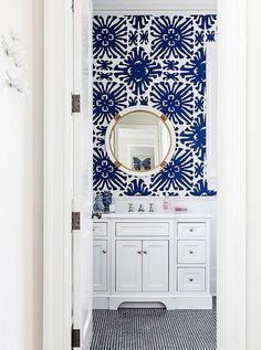 "Obsessed with the bold cobalt blue and white geometric sunburst patterned wallpaper and shiny brass and chrome accents in this adorable bathroom.  Read more on our Style Guide, ""Inside Sue De Chiara's Gorgeous Connecticut Home That's  Both Totally Traditional and Full-On Fun!"""