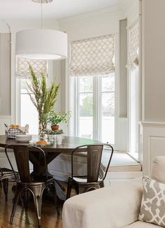 Transitional bay window breakfast nook is filled with a bay window bench under windows dressed in white and tan wedding circles roman shade facing an oval trestle dining table lined with Tolix Chairs illuminated by a white drum pendant.:
