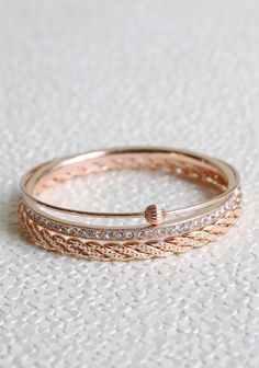 "Romance In The Summer Bangles 26.99 at http://shopruche.com. This set of three beautiful rose gold hued bangles feature glittering rhinestones, braided detail, and a beaded accent.2.75"" wide"