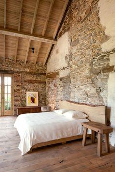 Simple pero espectacular dormitorio en una reforma rústica. Muebles de madera serrada, suelos y techos de madera, muros de piedra y ladrillo vistos...
