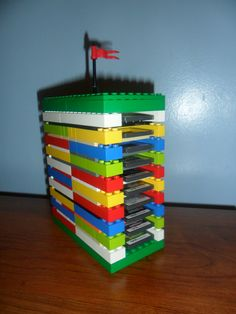 """My Lego-crazy son and I built our own Nintendo DS game tower with random Legos.  His DS game disks were always scattered, so we decided we needed something like a cd tower.  We made it so that each end holds 10 games (and we can always add layers on top if he needs more """"shelves"""")."""