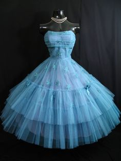 An absolutely gorgeous original 1950's party dress in a combination of peacock blue tulle, satin and embroidery. What a statement this gown would make at the approaching prom season ! The color is vibrant, highly unusual and stunning. It is perhaps best described as a very deep turquoise, with shades of teal. The style typifies the 50's - oh so feminine and figure flattering - perfect to accentuate a narrow waist.