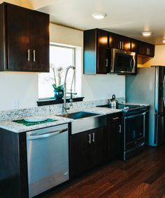 The gourmet kitchen is equipped with Whirlpool Gold Series appliances, granite counters, a farmhouse sink, and soft close upper and lower cabinets.