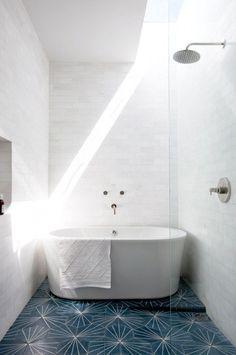 White bathroom with freestanding bathtub and blue tiled floor