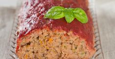 Marriage meatloaf cooked and ready to eat as it sits on a glass platter with a green basil leave as a garnish on the top. Red sauce covers the meatloaf.