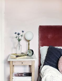 Wall painted in Beckers' muted pink Puderrosa 673, beautifully matched with burgundy velvet headboard in the bedroom of Swedish blogger Emma's Vintage.