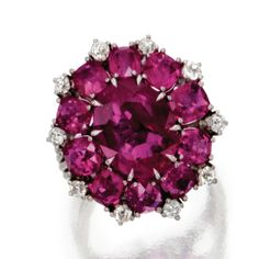PLATINUM, RUBY AND DIAMOND RING, CIRCA 1940    Set in the center with an oval ruby weighing approximately 5.05 carats, framed by smaller oval rubies weighing approximately 5.00 carats, accented by small round diamonds weighing approximately .50 carat