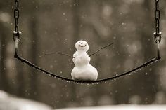 Happy Snowman on a swing with no idea spring is just around the corner