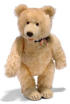 A STEIFF TEDDY BABY, (7340,2), jointed, salmon gold mohair, brown and black glass eyes, inset short mohair muzzle and top of feet, open mouth, brown and black stitching, squeaker, blue collar, script button with yellow cloth tag, chest tag and US-zone tag in arm seam, 1950s --15½in. (39.5cm.) high (slight wear and surface burn to one hand pad)
