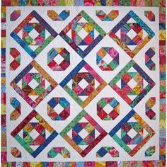 """This Accuquilt quilt pattern features jewel tone scraps that """"sizzle"""" when set onto a plain white fabric background. The quilt blocks are set on point with"""