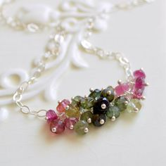 This gemstone necklace is a lovely combination of pinks and greens. A loose cluster of gorgeous tourmalines is centered on sterling silver cable