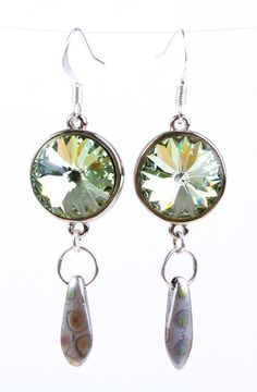 As nothing is complete without crystal sparkles, these are placed in a silver color metal bezel framing a beautiful chrysolite green Swarovski rivoli crystal functioning as a link connector for a single glass teardrop dagger in silver metallic color with peacock prints dangling beneath on a silver color metal ring. Handmade in USA.  Length: 2 1/4  Check the store for other color variations and shapes.  No shipping charge on all the items in the store.