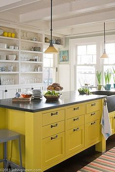 Great way to spruce up an all-white kitchen -- a yellow island!  Could also use an old dresser -- something repurposed and lacquered a bright color.