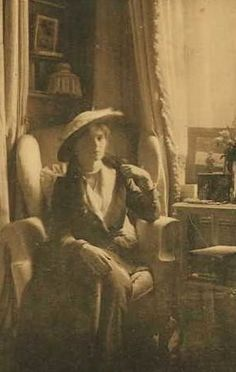 Olga dressed up as a young lady, sitting in the family chair.
