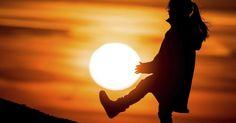 Uma menina parece segurar o sol com as mãos preparando-se para chutá-lo, como se ele fosse uma bola. Apenas um entardecer em Sieversdorf, na Alemanha