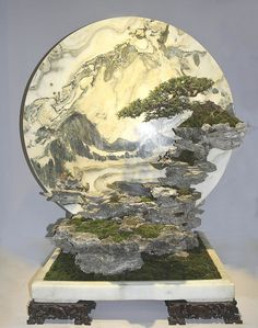 """Bigua Penjing or Wall-Hanging Penjing. - Is one of the """"styles"""" of Chinese penjing, which means the display is hung, could be on the wall, at the floor, with foot figures or supporting stones. Penjing Bigua usually made with a panoramic background, could be a painting, the composition of the rocks or calligraphy etc. and can be one or more trees in that form of grouping."""