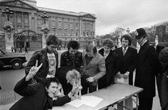 10 Mar 1977, London, England, UK — The punk rock group, The Sex Pistols, are about to be moved by a policeman as they sign a copy of their new recording contract with A & M Records outside Buckingham Palace.