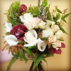 Bridesmaid or Bride's bouquet featuring white, green and burgundy. pieris, callalilies heather, leucothoe, cymbidiumorchids, moluccella