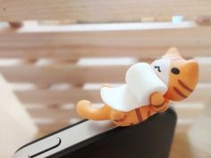 Cute Cat playing with papper roll Dust plug. iPhone by Yokozo, $3.90
