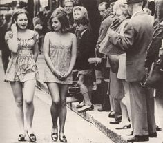 Two girls draw attention as they walk the street of Cape Town, South Africa [1965].