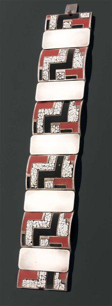 """RARE et LARGE BRACELET articulé en argent. Il comporte cinq motifs rectangulaires à décor géométriques en laque noire et corail et en laque blanche « coquille d'oeuf ». (restaurations). Epoque ART DECO. Dimensions : 19 x 3, 5 cm. Réf : à rapprocher pour le décor et les couleurs d'un étui par Paul BRANDT. Exposition : Musée des Arts Décoratifs"""" Bijoux Art Déco"""", Paris 2009."""