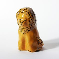 A pensive fellow. Probably calm in a crisis. Made of white stoneware clay, he's hand-painted in tan and black and coated with a smooth clear glaze.Only one lion is available. It measures approximately 8.5cm in height, and the base is 5.5cm at its widest point. The underside is slightly hollowed out and unglazed, and all glaze is non-toxic. My ceramics are made by hand and all subsequent details add to their charm. I don't set out to make perfect, smooth objects, but the thin...