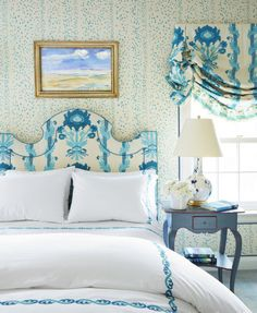 Walls are upholstered in China Seas' Rio, and the headboard and Roman shade are in Henriot Floral by Quadrille. Bedding by Fine Linens. ~ Christopher Maya in HB.