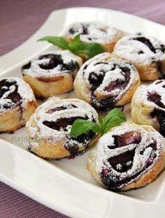 Francuskie jagodziankiSkładniki: – 1 płat ciasta francuskiego – 150 g serka waniliowego albo homogenizowanego – 50-70 g jagód – cukier puder do posypania