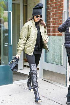 Kendall Jenner wears a black sweater, bomber jacket, leggings, thigh-high Chanel boots, a mini Birkin bag, aviator sunglasses, and a beanie