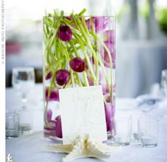 Submerged tulips in clear vases topped some of the tables, and were surrounded by votive candles. The table numbers were held up by starfish, adding to the beachy feel.