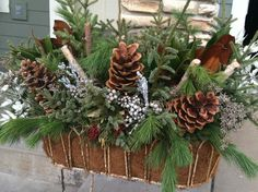 Wrought Iron stand with winter greens, sugar pine cones and assorted mixed berry