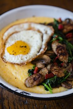 Cheesy polenta topped with spinach, mushrooms, sun dried tomatoes, chicken sausage and topped with a crispy fried egg.