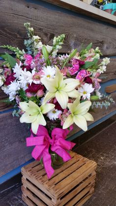 This arrangement features white lilies, pink alstroemeria, dark pink carnations, white snapdragons, white stock, eucalyptus, white daisies, and pink waxflower.  www.bloominggalsbouquets.com http://on.fb.me/1BT3HNz