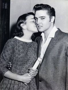 A fan stealing a kiss from a young Elvis Presley